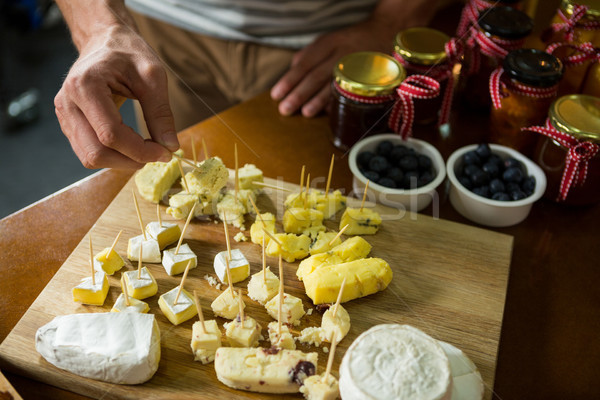 Staff arranging piece of cheese on wooden board in grocery shop Stock photo © wavebreak_media