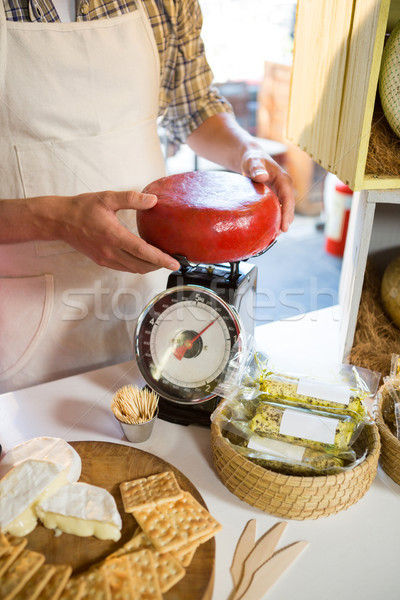 Mid-section of staff weighing gouda cheese at counter Stock photo © wavebreak_media