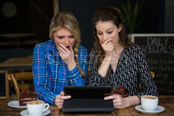 Shocked women using tablet computer in coffee shop Stock photo © wavebreak_media
