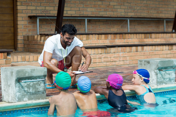 Instructor writing on clipboard while explaining little swimmers at poolside Stock photo © wavebreak_media