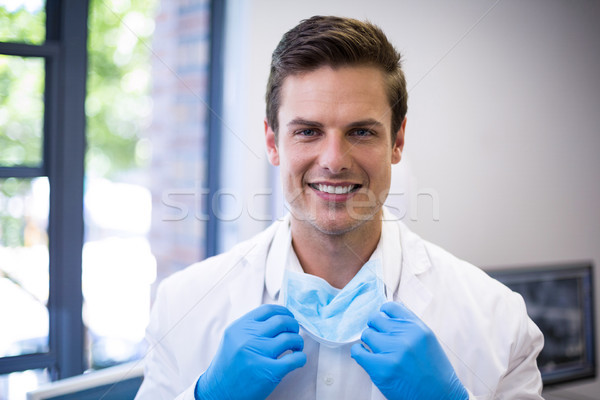 Portrait of happy dentist holding surgical mask Stock photo © wavebreak_media