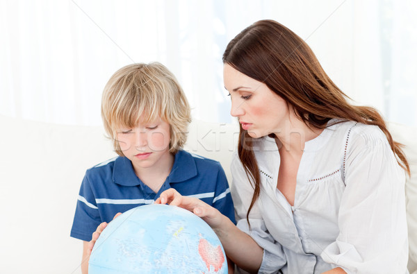 Captivated child looking at a terrestrial globe with his mother Stock photo © wavebreak_media