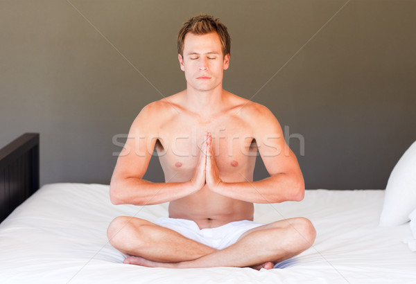 Young boy doing yoga on bed with clossed eyes Stock photo © wavebreak_media