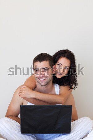 Smiling couple using a laptop on a bed Stock photo © wavebreak_media