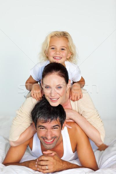 Radiant family lying on a white bed Stock photo © wavebreak_media
