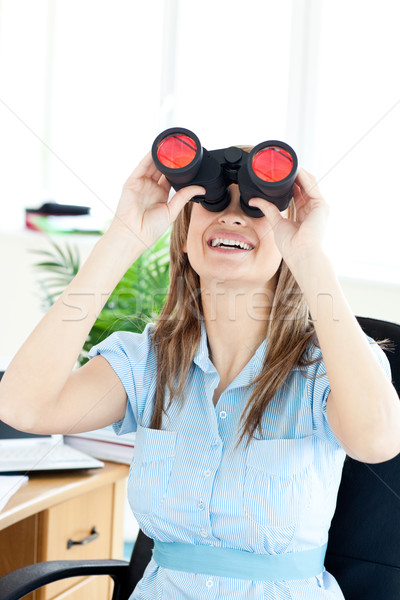 Radiant woman sitting on a chair in her office and looking through binoculars Stock photo © wavebreak_media