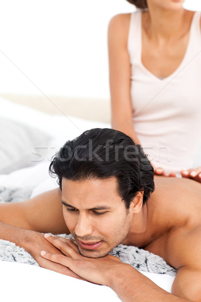 Close up of a woman doing a massage to her boyfriend lying on their bed at home Stock photo © wavebreak_media
