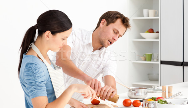 Man putting salt and pepper while his girlfriend stiring the sauce in the kitchen Stock photo © wavebreak_media