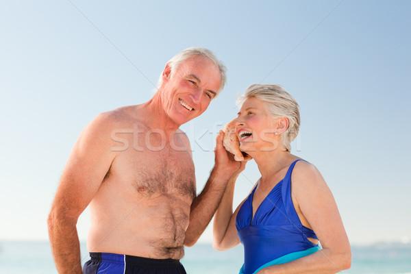 Emeryturę para słuchania powłoki plaży uśmiech Zdjęcia stock © wavebreak_media