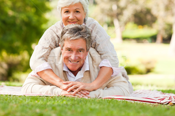 Stock photo: Mature couple lying down in the park