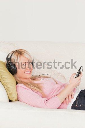 Boa aparência mulher ouvir música fones de ouvido sessão sofá Foto stock © wavebreak_media