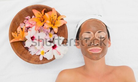 Young blonde woman lying down near flower petals in a Spa centre Stock photo © wavebreak_media