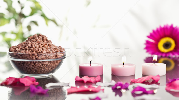 Lighted pink candles with petals and a bowl of gravel with a pink gerbera in the background Stock photo © wavebreak_media