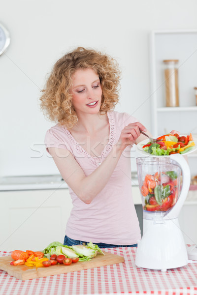 Beautiful blonde woman using a mixer in the kitchen in her appartment Stock photo © wavebreak_media