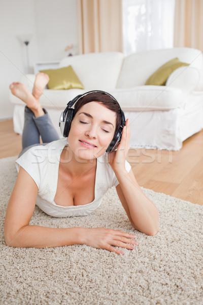 Retrato encantado morena ouvir música tapete menina Foto stock © wavebreak_media