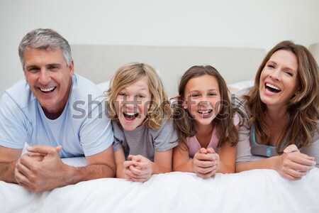 Stock photo: Laughing Friends lounging on a sofa watching a movie in a living room