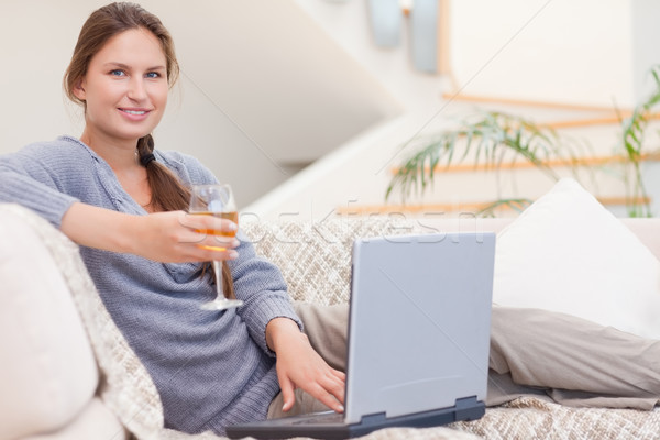 Stock photo: Woman having a glass of wine while using her laptop in her living room