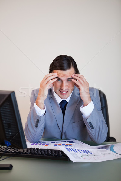 Stock photo: Frustrated young businessman working on statistics