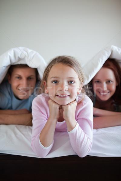 Glimlachend meisje bed dekken samen ouders Stockfoto © wavebreak_media