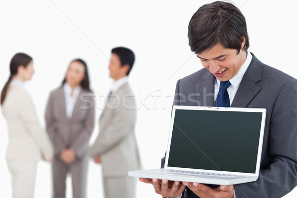 Salesman showing laptop screen with team behind him against a white background Stock photo © wavebreak_media
