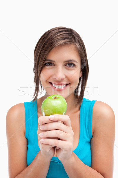 Teenager smiling while holding a green apple with her hands crossed Stock photo © wavebreak_media