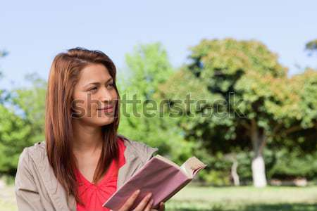 Young woman joyfully reading a book with the wind blowing through her hair in a bright parkland area Stock photo © wavebreak_media
