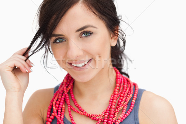 Smiling blue eyed woman with a red bead necklace against white background Stock photo © wavebreak_media