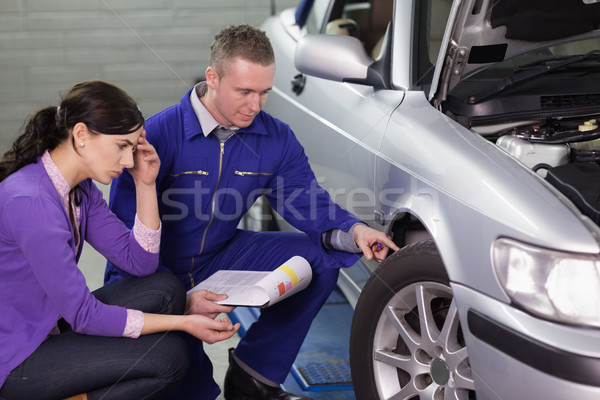 Mécanicien regarder voiture roue client garage Photo stock © wavebreak_media