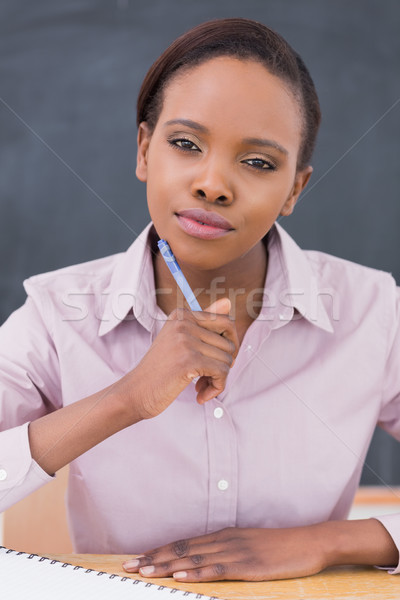 Black teacher looking at camera while thinking in a classroom Stock photo © wavebreak_media