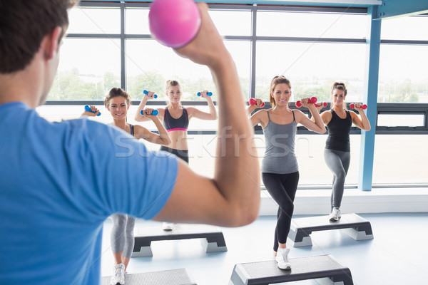 Trainer teaching his aerobics class while lifting weights in gym Stock photo © wavebreak_media