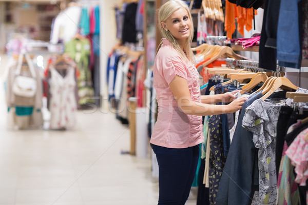 Woman is smiling by the clothes rail in a clothes shop Stock photo © wavebreak_media