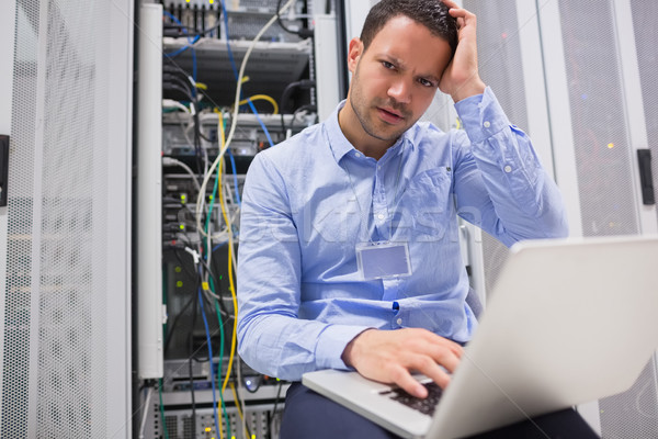 Technician getting frustrated with laptop over servers in data center Stock photo © wavebreak_media