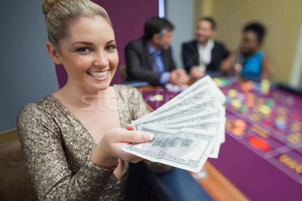 Woman holding out fan of dollars in casino Stock photo © wavebreak_media