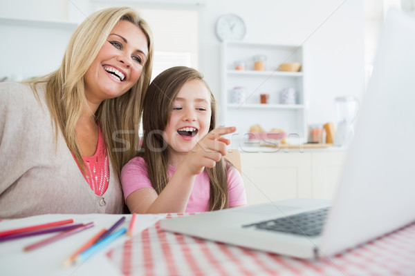 Mothe and child sitting at the kitchen table while looking at the laptop and laughing Stock photo © wavebreak_media