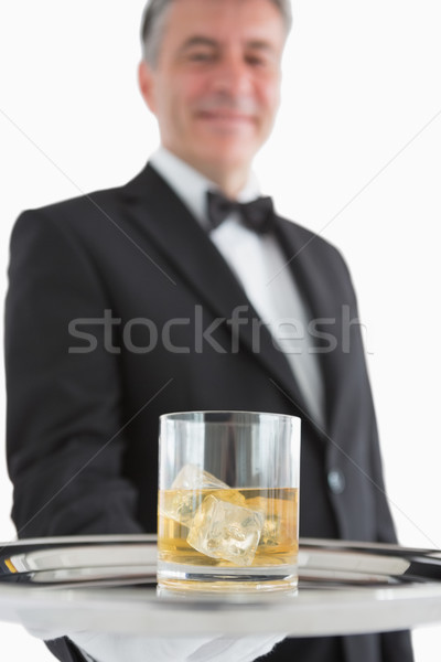 Smiling man in suit holding glass of whiskey on silver tray Stock photo © wavebreak_media