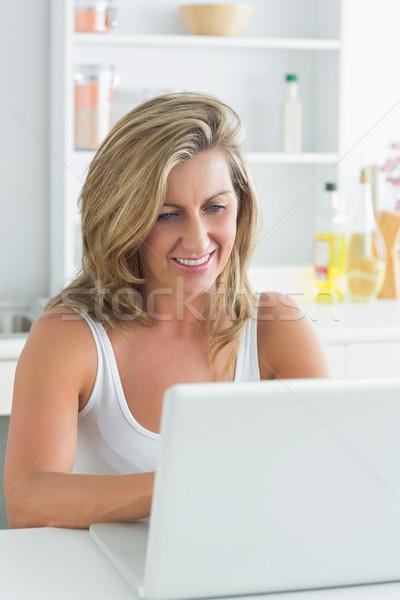 улыбающаяся женщина используя ноутбук кухне компьютер женщину счастливым Сток-фото © wavebreak_media
