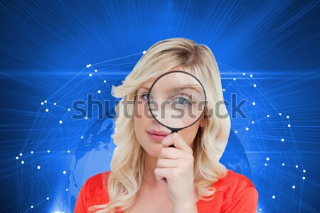 Blonde looking through magnifying glass Stock photo © wavebreak_media