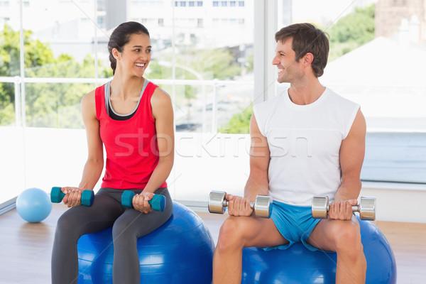 Happy couple lifting dumbbells while sitting on fitness balls in Stock photo © wavebreak_media