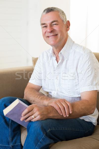 Senior man with book siting on sofa Stock photo © wavebreak_media