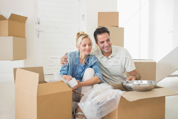 Smiling couple unpacking boxes in a new house Stock photo © wavebreak_media