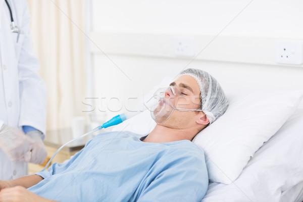 Male doctor adjusting oxygen mask on patient Stock photo © wavebreak_media