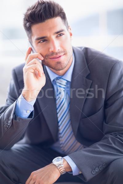 Happy businessman sitting on sofa making a call Stock photo © wavebreak_media