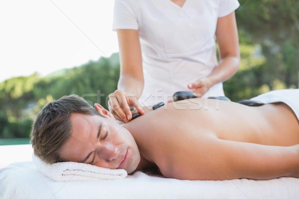 Handsome man getting a hot stone massage poolside Stock photo © wavebreak_media