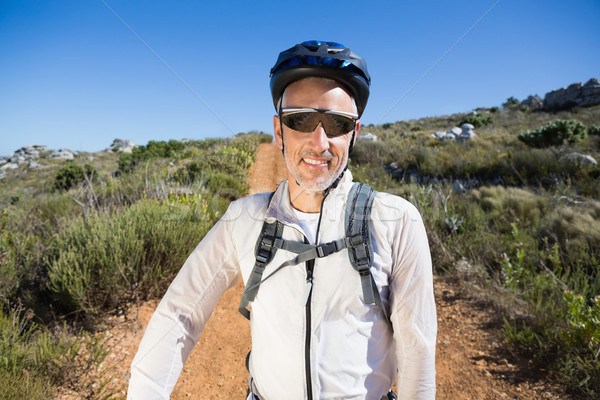Fit cyclist smiling at the camera on country terrain Stock photo © wavebreak_media