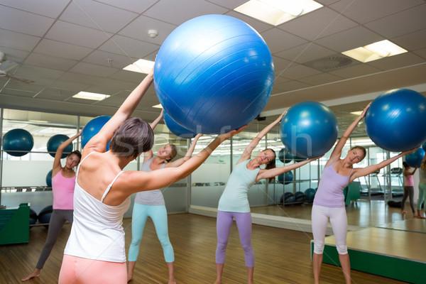 Fitness class holding up exercise balls in studio Stock photo © wavebreak_media