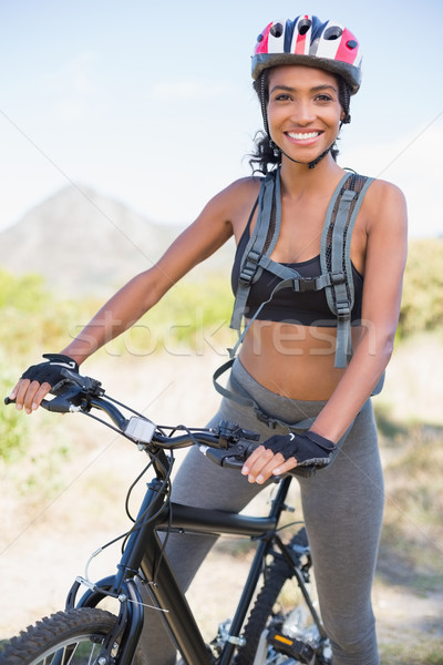 Fit woman going for bike ride smiling at camera Stock photo © wavebreak_media