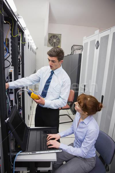 Team of technicians using digital cable analyser on servers Stock photo © wavebreak_media