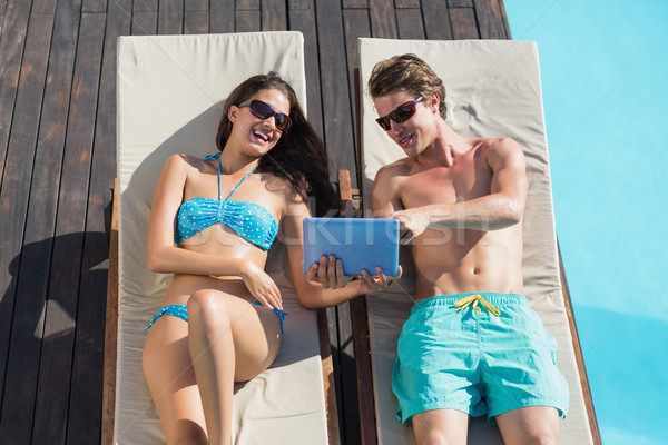 Couple using digital tablet on sun loungers by swimming pool Stock photo © wavebreak_media