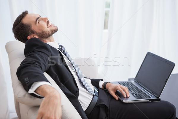 笑みを浮かべて ビジネスマン ラップトップを使用して ソファ ホーム リビングルーム ストックフォト © wavebreak_media