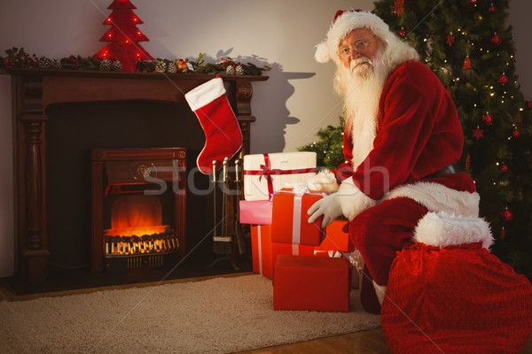 Cheerful santa delivering gifts at christmas eve Stock photo © wavebreak_media